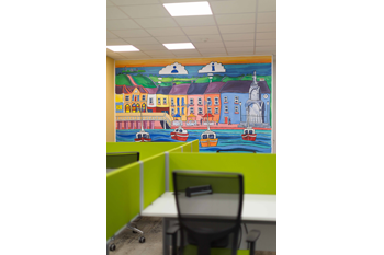 Kilrush Digital Hub hot-desk with bespoke mural painted by Dave O'Rourke in the background